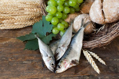 9279319-bread-and-fish-with-wine-grapes-symbolizing-the-miracles-of-jesus-christ